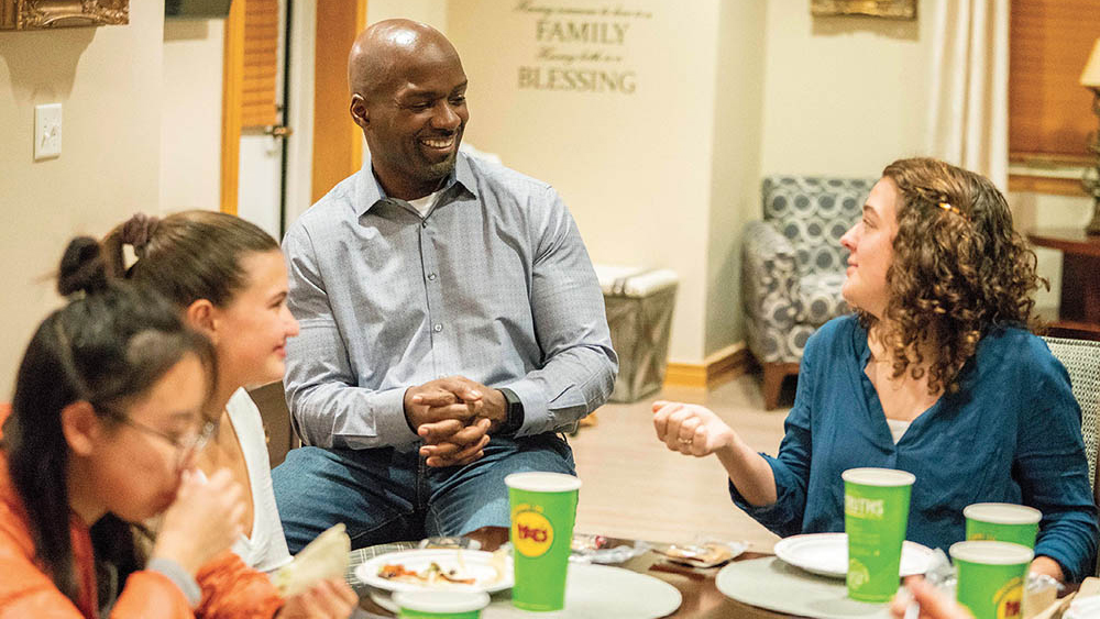 Noble (center) visits with Clara Leonard (right), a junior resident adviser in Stambaugh House, and first-years Catherine Crawford and Lauren Cheng during a dinner in the faculty residence.
