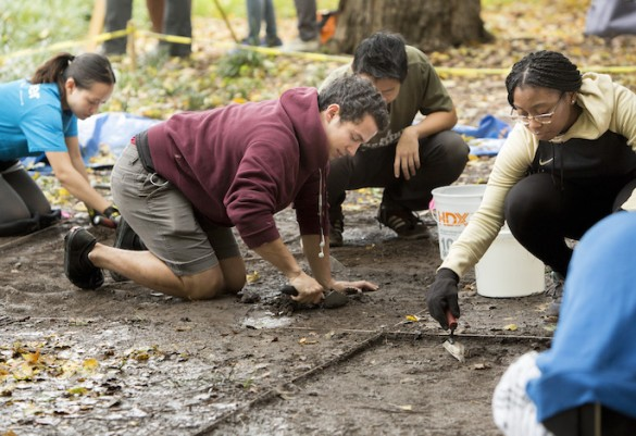 students on hands and knees on wet dirt
