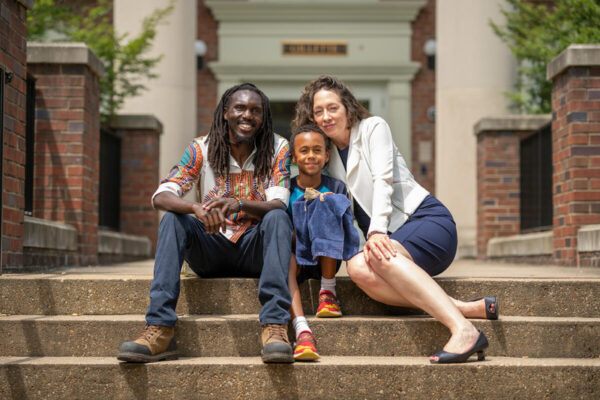 Carol Ziegler, Faculty Head of Gillette House, with her family Kipkosgei Magut, left, and Ezra Magut and pet lizard Stripes outside Gillette House on the Martha Rivers Ingram Commons.