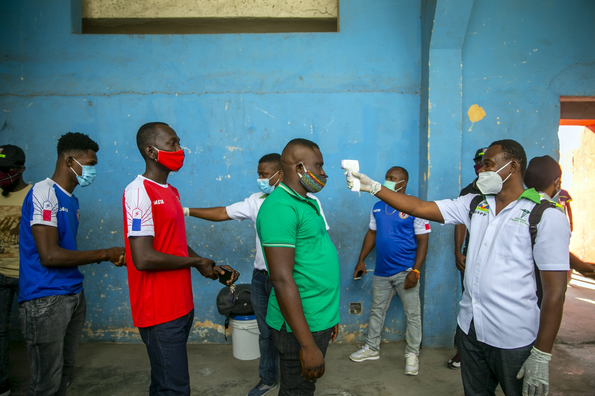 Health ministry workers check the temperature of mask-wearing fans prior to the start of a soccer match in Port-au-Prince, Haiti, on March 25, 2021.