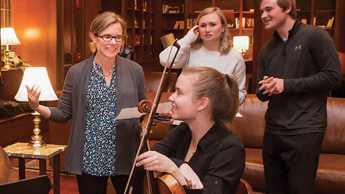 Igo (left) chats with students from the Blair School of Music performing at Bronson. The event, called the Blair Salon, was organized by senior resident adviser James Dohm (right).