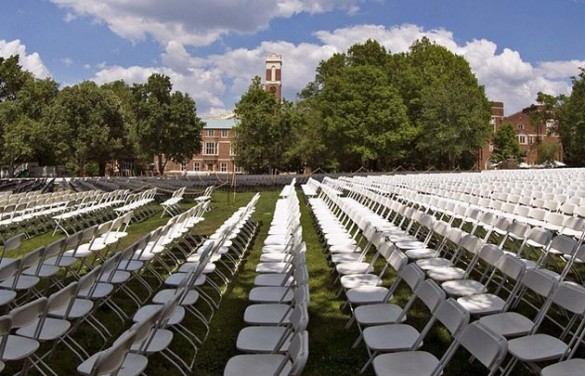 Chairs set up on Alumni Lawn ahead of Commencement exercises, with a view of the Kirkland clock tower in the distance.