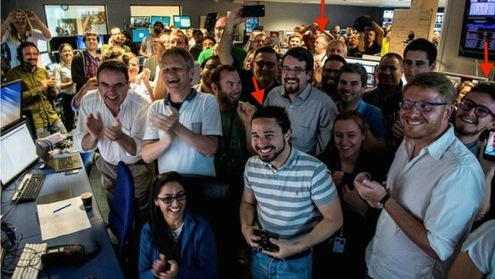 group shot of researchers cheering in control room