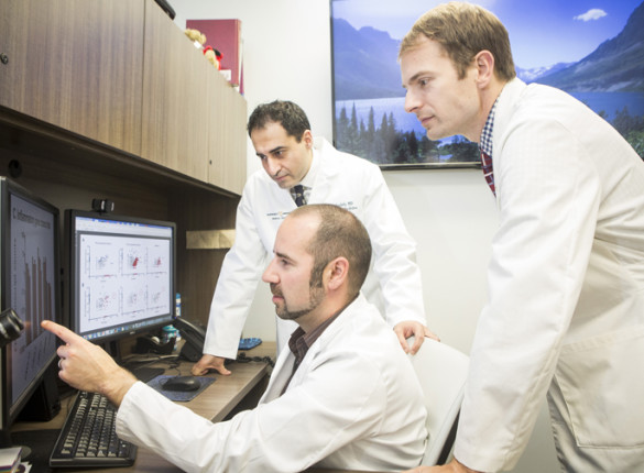 Justin Balko, Pharm.D., Ph.D., seated, Javid Moslehi, M.D., left, and Douglas Johnson, M.D., MSCI, review data on rare cardiac side effects linked to cancer immunotherapy combination therapy. (photo by Susan Urmy)