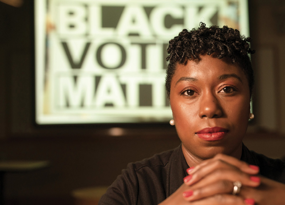"""photo of Charlane Oliver in front of a sign that says """"Black Votes Matter"""""""