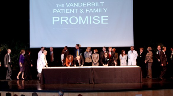 Attendees of last week's Winter Clinical Enterprise Leadership Assembly sign a banner-sized copy of the new Vanderbilt Patient and Family Promise. (photo by Susan Urmy)