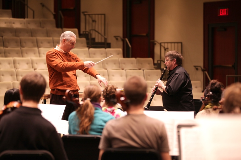 Composer directing clarinetist and other musicians