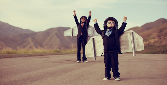 two cute kids wearing homemade jetpacks in the desert