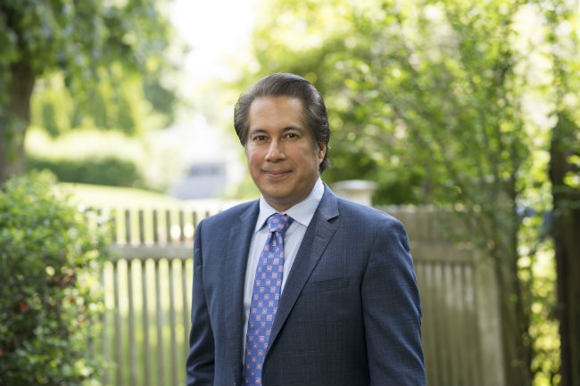 horizontal photo of Blair School Dean Frank Candelaria in front of picket fence