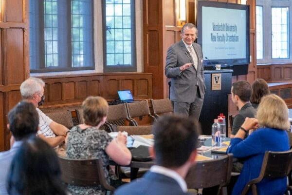 photograph of Chancellor Daniel Diermeier speaking to new faculty seated at round table