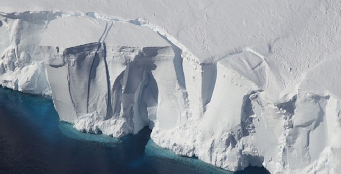 satellite image of antarctic ice sheet fracturing at the edge of the sea