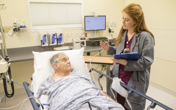 Vanderbilt University student Kate Sborov works with patient Wendell Crouch through VUMC's new Immersion in Emergency Care Research course for undergraduate students. (photo by John Russell)