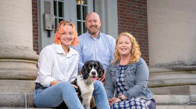Peabody professor Emily Pendergrass with her husband, Josh, daughter, Kat and dog, Scooter outside West House where she will serve as Faculty Head of House.