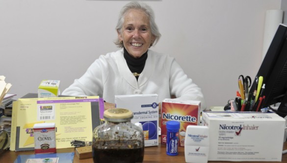 Among the many tools Barbara Forbes, MSN, uses to help people kick the habit is a large jar of tar, foreground, that represents the amount of tar a smoker will ingest in a year. (photo by Joe Howell)