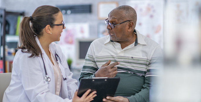 Older African American man and a young white female doctor discussing his health record in a doctor's office.