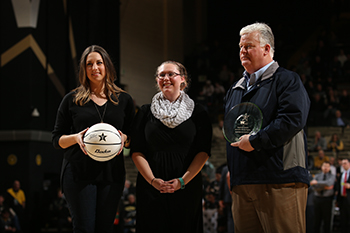 Sarah Sturgeon, center, accepts the award for last year's Vanderbilt Basketball Sustainability Competition on behalf of Maulik Patel's Lab by Chelsea Hamilton of SEMO and Robert Cheney of Waste Management. (John Russell/Vanderbilt University)