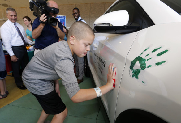 Gabe Daniels, 12, who is battling cancer with the help of Monroe Carell Jr. Children's Hospital at Vanderbilt, places his painted handprint on the official Hyundai Hope on Wheels vehicle as a symbol of his journey. (photo by Steve Green)