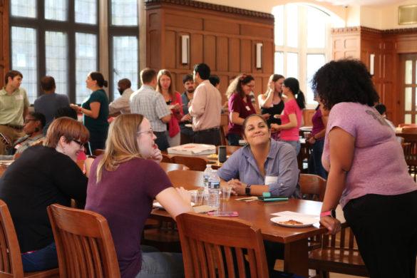 diverse postdocs gathering in Alumni Hall for delicious pizza