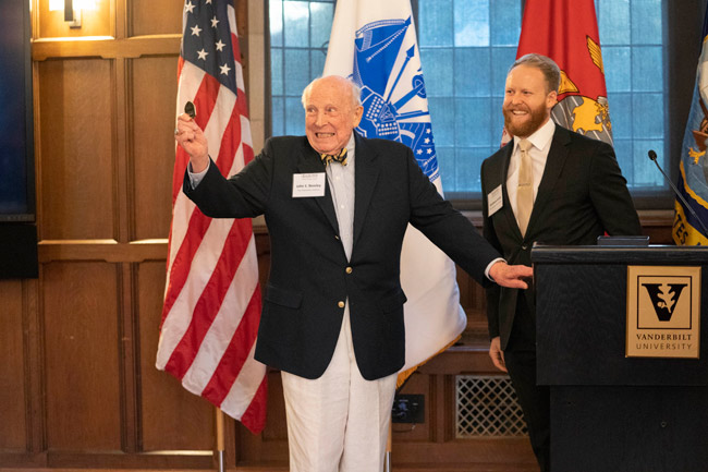 Vanderbilt alumnus and longtime administrator John S. Beasley II (left) receives a Bass Military Scholar challenge coin from inaugural Beasley Scholarship recipient Matthew Smith, a School of Medicine student and former Navy SEAL. (Joe Howell/Vanderbilt)
