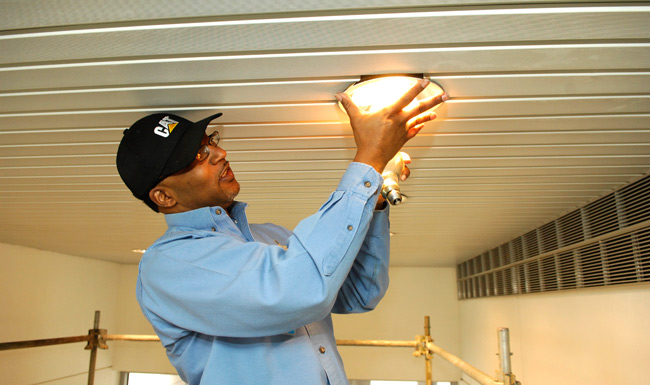 Anthony Hayes of VUMC Plant Services' electrical shop installs LED energy efficient light bulbs at Eskind Biomedical Library. (Anne Rayner/Vanderbilt)