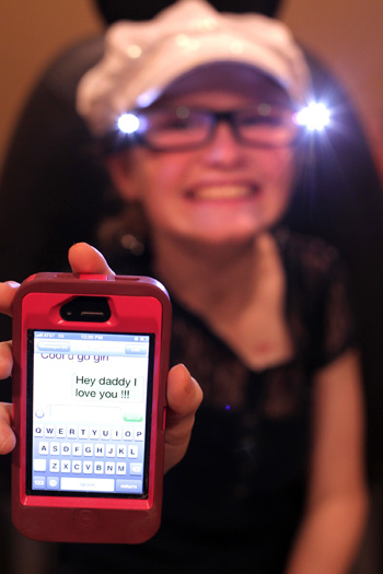 Alexis London shows off the text she sent her father after receiving her Low Vision Readers. (photo by Steve Green)