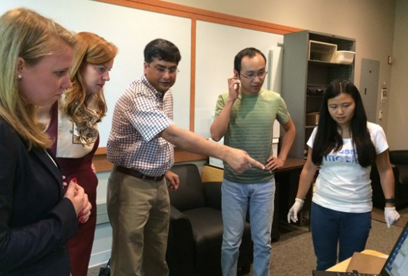 Professor of Mechanical Engineering Nilanjan Sarkar (center), accompanied by Ph.D. students Dayi Bian (second from right) and Jian Fan (far right), shows Kayla McMurry (far left) and Mackensie Burt (second from left) from Sen. Lamar Alexander's staff the simulator that he developed with researchers at the Vanderbilt Kennedy Center to help teenagers with autism learn to drive. (Vanderbilt University)