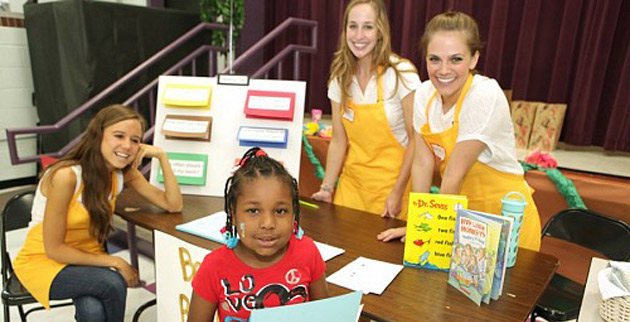Rising kindergartener Jariah Hendricks finishes learning about healthy bedtime routines from VUSN students at the Kindergarten Kick-Off at Kirkpatrick Elementary School. Students pictured are, from left, Allie Morrison, Melanie Parker and Mallory Moore. (Anne Rayner/Vanderbilt)