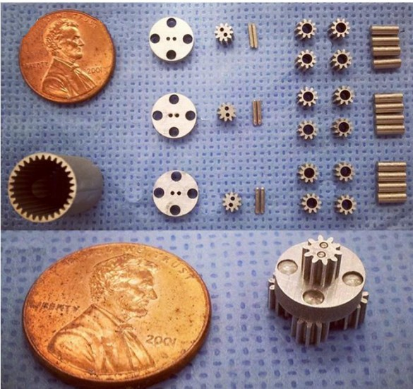 components laid out on table next to a penny for scale