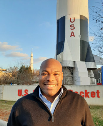 rocket scientist Patrick Taylor in front of rocket at U.S. Space and Rocket Center