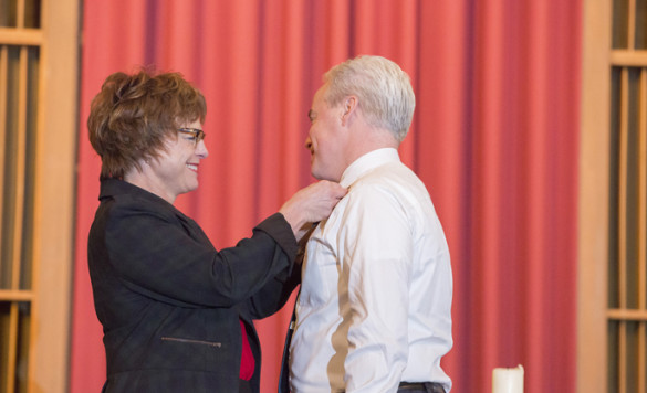 Terri Allison, DNP, ACNP-BC, presents Duke Chenault, ACNP-BC, with a pin guard in recognition of his completion of the School of Nursing's Doctor of Nursing Practice (DNP) program. (photo by Susan Urmy)