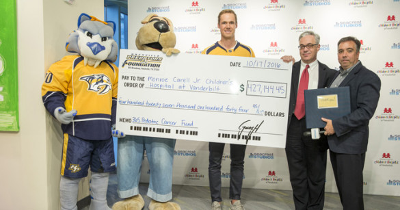 The Nashville Predators presented a check this week to Monroe Carell Jr. Children's Hospital at Vanderbilt to help fund pediatric cancer research. On hand for the ceremony were, from left, Predators mascot Gnash, Children's Hospital mascot Champ, Predators goaltender Pekka Rinne, Steven Webber, MBChB, MRCP, and Predators President and CEO Sean Henry. (photo by John Russell)