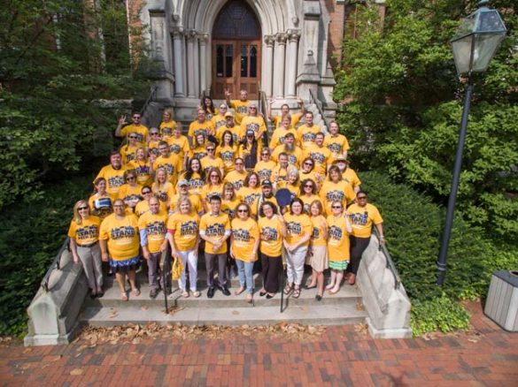 Members of the Division of Communications and the Office of the Chancellor wear their #UnitedInGold T-shirts on the steps of Kirkland Hall. (Daniel Dubois/Vanderbilt)