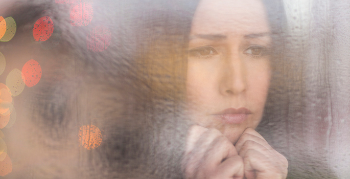 sad woman looking through a window