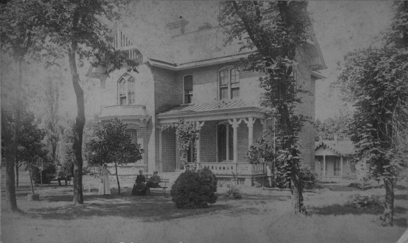 Black and white old fashioned photo of house and cottage with residents standing in yard