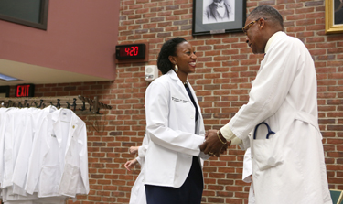 Leah Chisholm is congratulated by Andre Churchwell, M.D., after receiving her white coat. (photo by Anne Rayner)