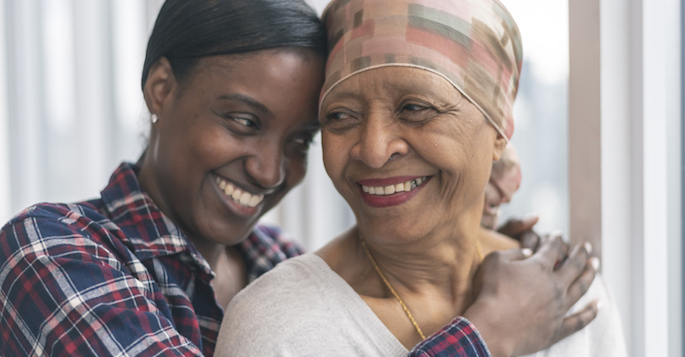 A black senior woman with cancer is wearing a scarf on her head. Her adult daughter is giving her a hug. Both women are smiling with gratitude and hope for recovery.