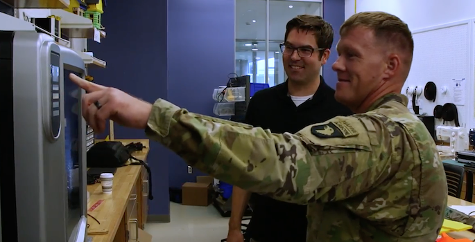 army guy pressing a button on a 3D printer while kevin galloway looks on