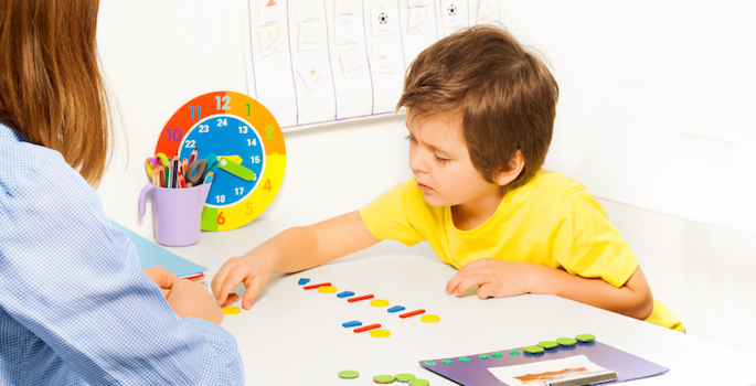 boy arranging colorful objects with therapist