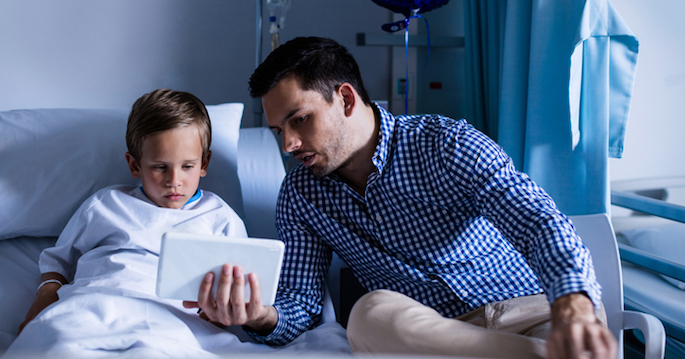 Father and son using digital tablet at hospital