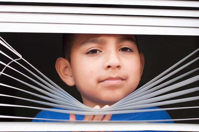 Boy looking through blinds