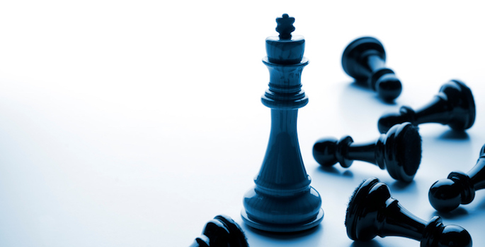 Black chess king surrounded by fallen black pawns