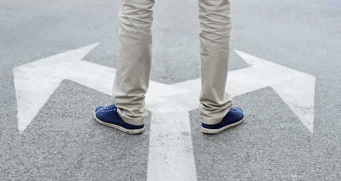 Decision concept - Man standing on arrows painted on asphalt.