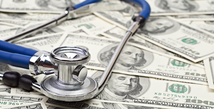 stethoscope resting on a pile of $100 bills