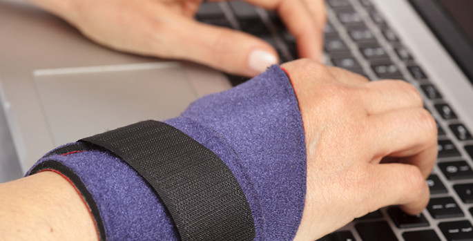 close-up of hand wearing wrist brace while typing