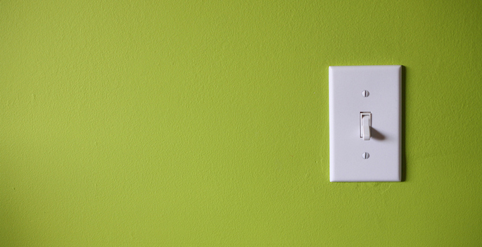 white light switch mounted on green wall