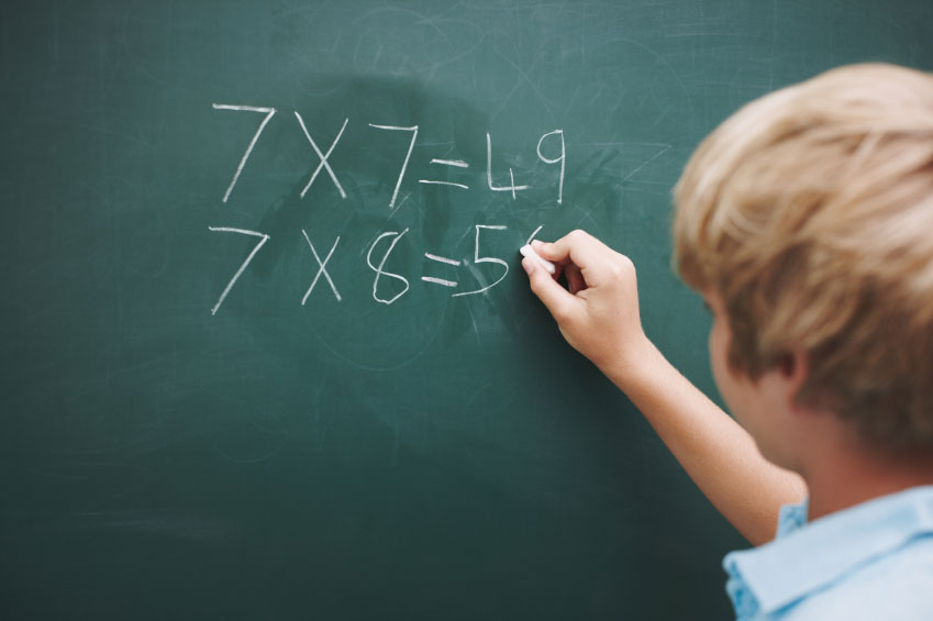 child writing math on blackboard