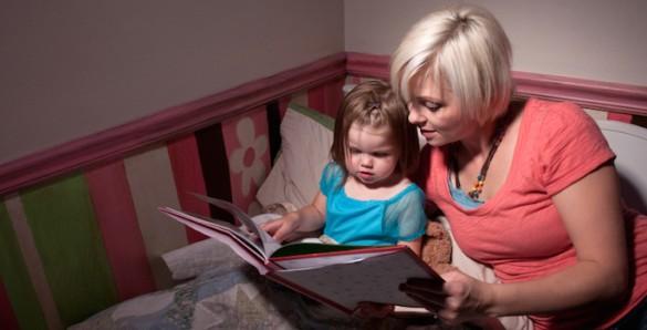 mom reading bedtime story to toddler girl