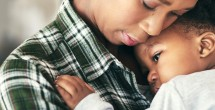 african american mom snuggling small child