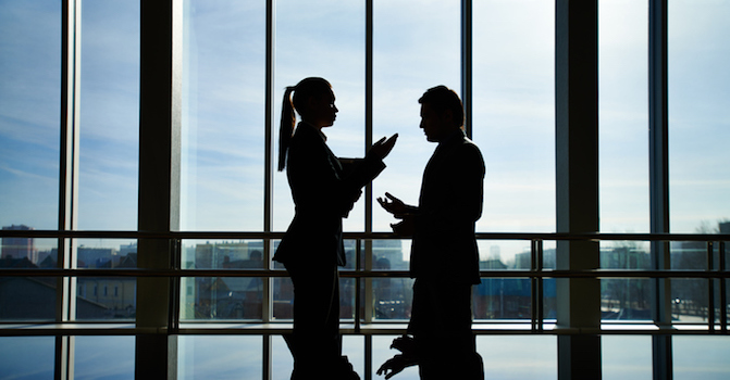 Silhouettes of businessman and businesswoman arguing standing by railing