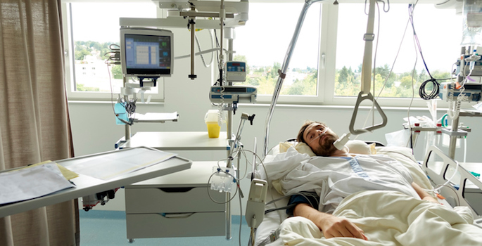 Young man waking up in a hospital bed after surgery. He's got a breathing tube in his nose and medical equipment around him.